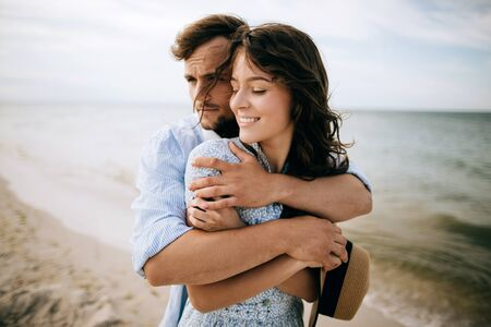 Romantic Happy Couple On The Beach At Sunset, man and woman hugging