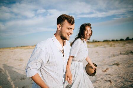 Happy couple walking on the sea beach. Sea travel and summer vacation Zdjęcie Seryjne