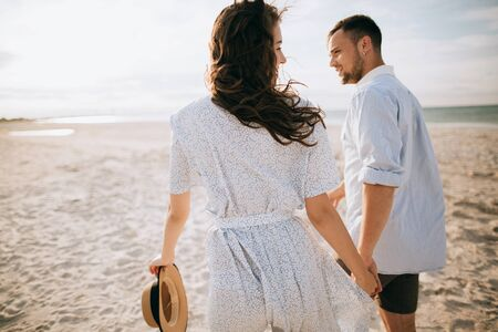 Young couple walking on the morning sea beach holding hands Zdjęcie Seryjne