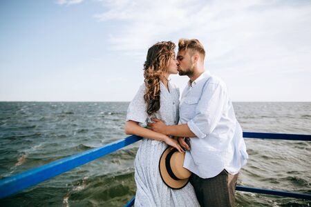 Young couple in love kissing and hugging on the sea pier. summer holidays