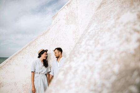 Young couple on the beach near the wall of the old lighthouse. Copispace