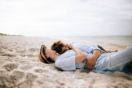 Man and woman lie on a deserted sea beach and hug. Summer vacation