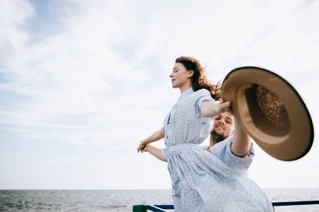 Young couple on the sea pier. The concept of freedom Zdjęcie Seryjne