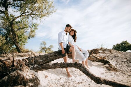 Happy young couple sitting on the beach on an old tree and hugging. Honeymoon at sea