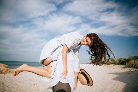Guy carrying a girl on his back, at the beach, outdoors. Love concept