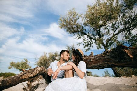 Young couple sitting on the beach near an old tree. Love concept Zdjęcie Seryjne