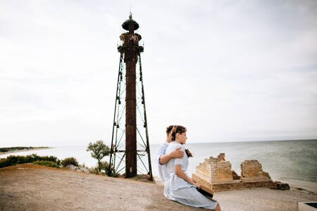 Young couple hugging on the background of an old lighthouse. The concept of summer vacation and love