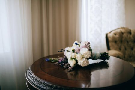 White wedding bouquet of peonies on a wooden table. Wedding accessories