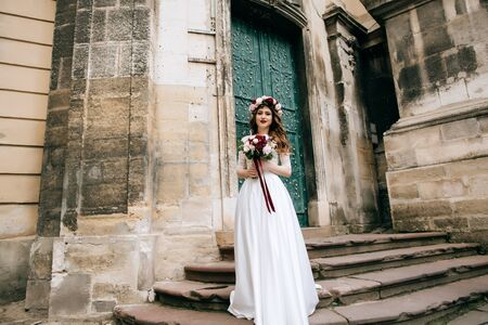 Beautiful bride portrait outdoors on the steps of the church in old city. Wedding concept Zdjęcie Seryjne