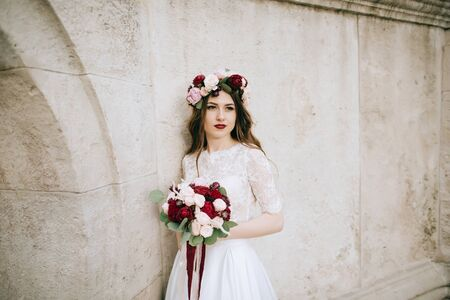 Bride portrait outdoors in a wreath and a wedding bouquet in hands. Wedding concept Standard-Bild