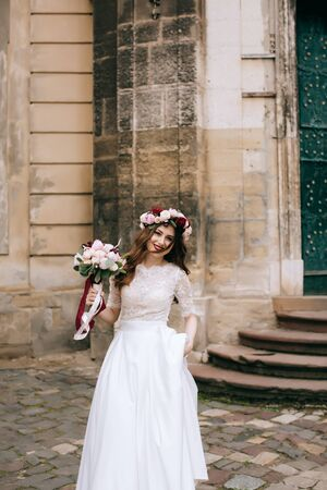 Beautiful bride in white dress with a bouquet of flowers and a wreath on the background of an old building