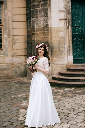 Beautiful bride with a bouquet of flowers and a wreath on the background of an old building Standard-Bild