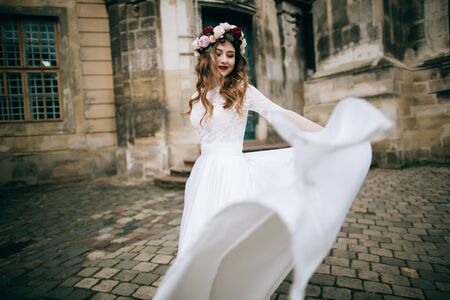 beautiful bride in a wreath dancing in the street