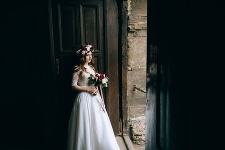Beautiful bride in a wreath with a bouquet in her hands Standard-Bild