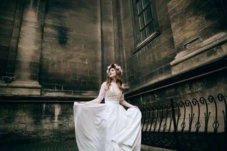 lonely beautiful bride in a white dress walking in old city. wedding concept Zdjęcie Seryjne
