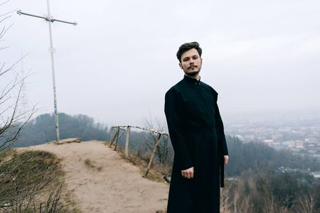 Portrait of a young serious Christian Catholic priest or pastor in a black robe outdoors