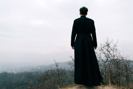 Portret przystojnego katolickiego brodatego mężczyzny księdza lub proboszcza pozowanie na zewnątrz w górach Zdjęcie Seryjne