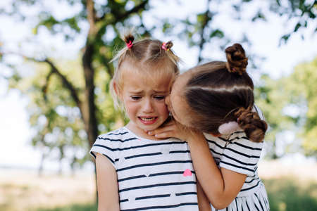 A little girl cries in the park, her older sister calms her down and kisses her
