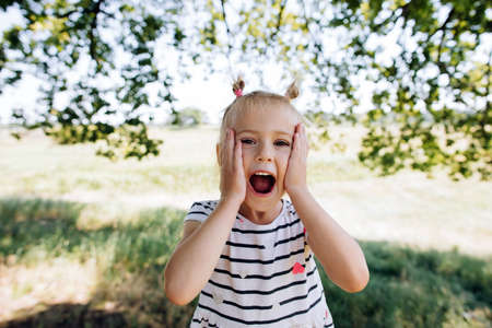 The child cries out in surprise and happiness. Happy and carefree childhood