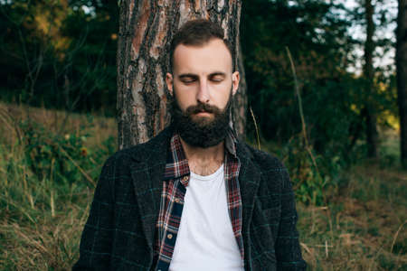 A young bearded man closed his eyes resting and dreaming in the woods. The concept of unity with nature