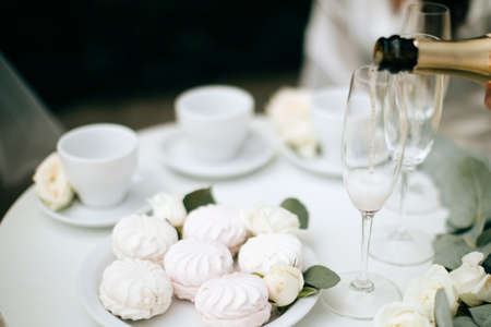White and pink marshmallows and champagne on the wedding table. Festive dinner