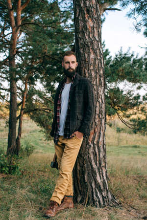 Portrait brutal bearded and moustached woodcutter hipster Gypsy man in the forest with ax