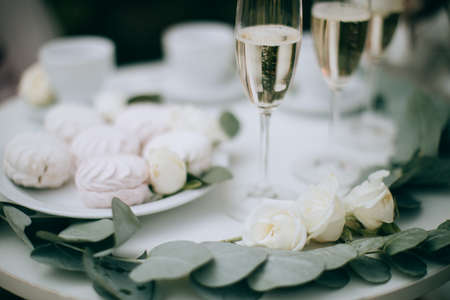 Marshmallows and glasses of champagne on a white table. Wedding decor