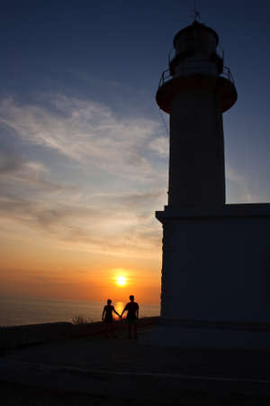 Lovers at sunset in the lighthouse photo