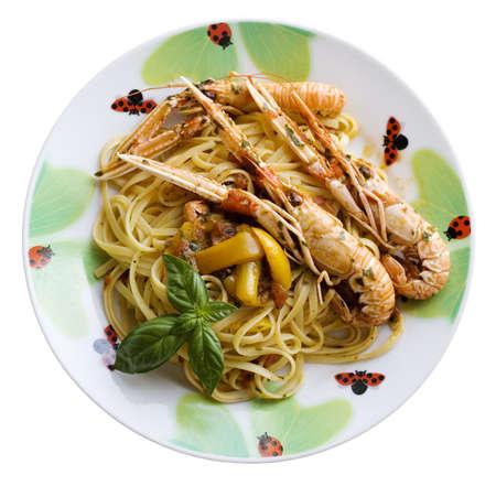 A dish of spaghetti with tomato sauce, basil, scampi and shrimp photo