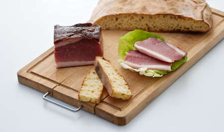 casein: Raw ham and sliced bread on a cutting board