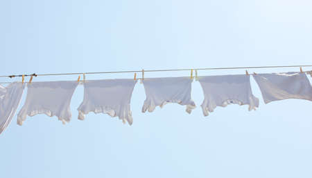 White t-shirt hanging to dry on a clothes-line. photo