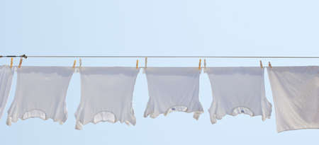 White t-shirt hanging to dry on a clothes-line. Standard-Bild