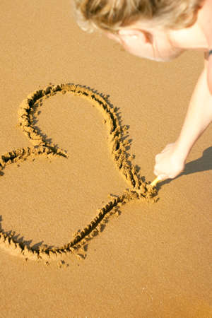 Girl drawing an Heart in the beach  photo