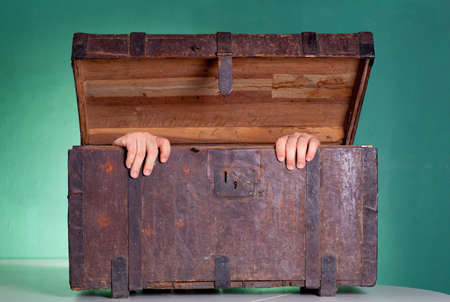 Hands coming out the Antique wooden trunk photo