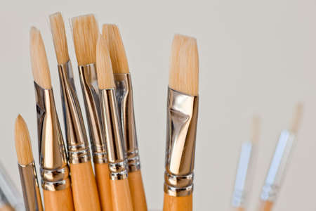 New paintbrushes in a old ceramic jar photo