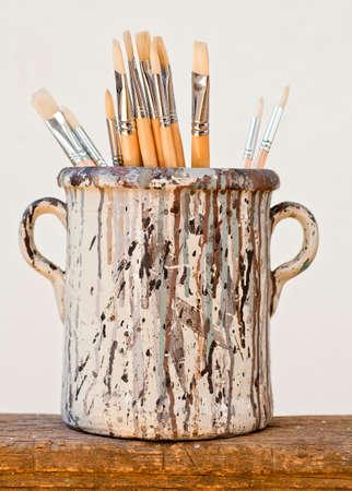 Neue Pinsel in einem alten Keramik Glas Standard-Bild
