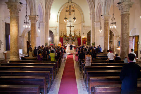 catholic mass: Interior of a christian church with a couple getting married Editorial