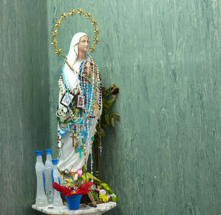 Statue of Virgin Mary covered with rosaries