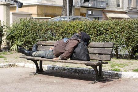 Homeless schläft auf der Bank Standard-Bild