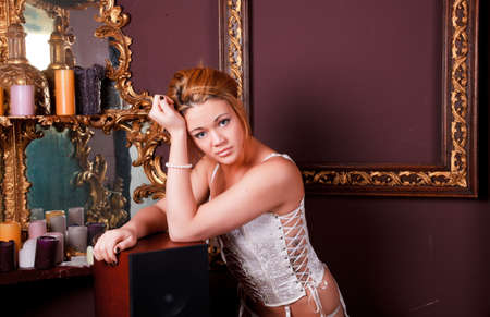 Sensual blonde girl in underwear next to a old mirror photo