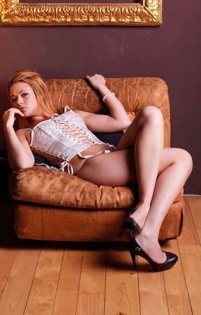 Sensual blonde girl in underwear on armchair photo
