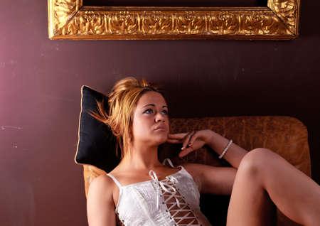 underclothes: Sensual blonde girl in underwear on armchair Stock Photo