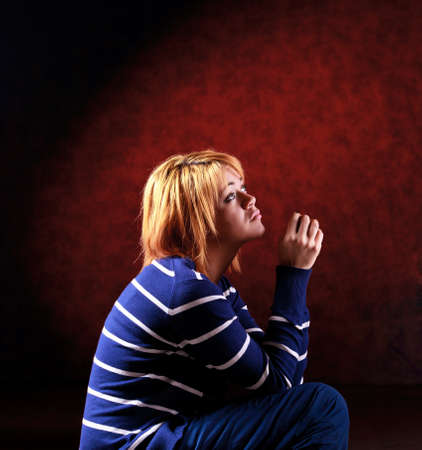 Girl sitting on the stool on red background photo