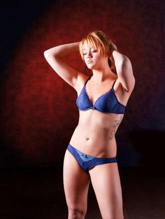 underclothes: Sensual blonde girl in underwear on dark background,