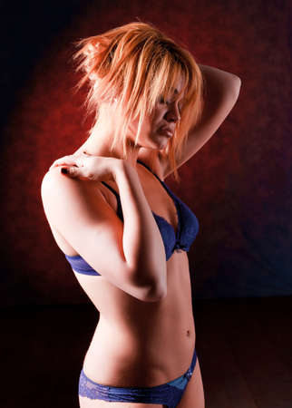 Sensual blonde girl in underwear on dark background, photo