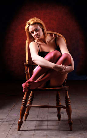 Sensual blonde girl in underwear on wooden chair photo