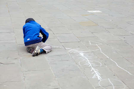 Child drawing in the street with chalks photo