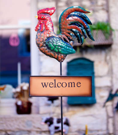 neighborly: Welcome sign with iron rooster Stock Photo