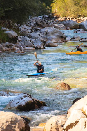 KOBARID, SLOVENIA - AUGUST 18: Two sport kayakers rowing in the Soca river, August 18, 2012 in Kobarid, Slovenia