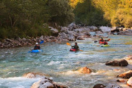 KOBARID, SLOVENIA - AUGUST 18: Sport kayakers rowing in the Soca river, August 18, 2012 in Kobarid, Slovenia